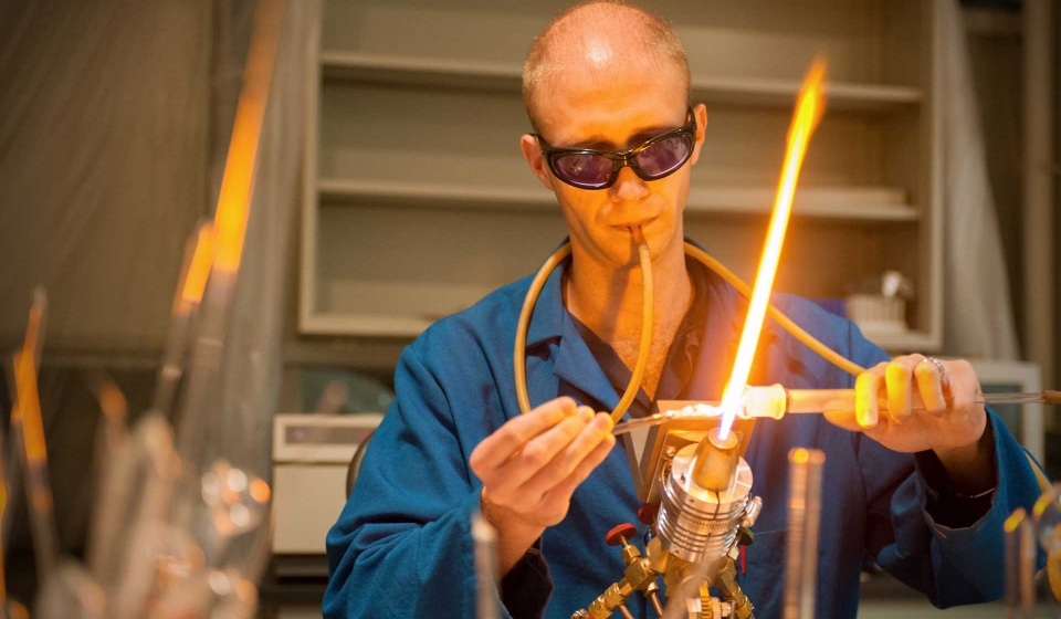 A Chemistry student blowing glass in a lab